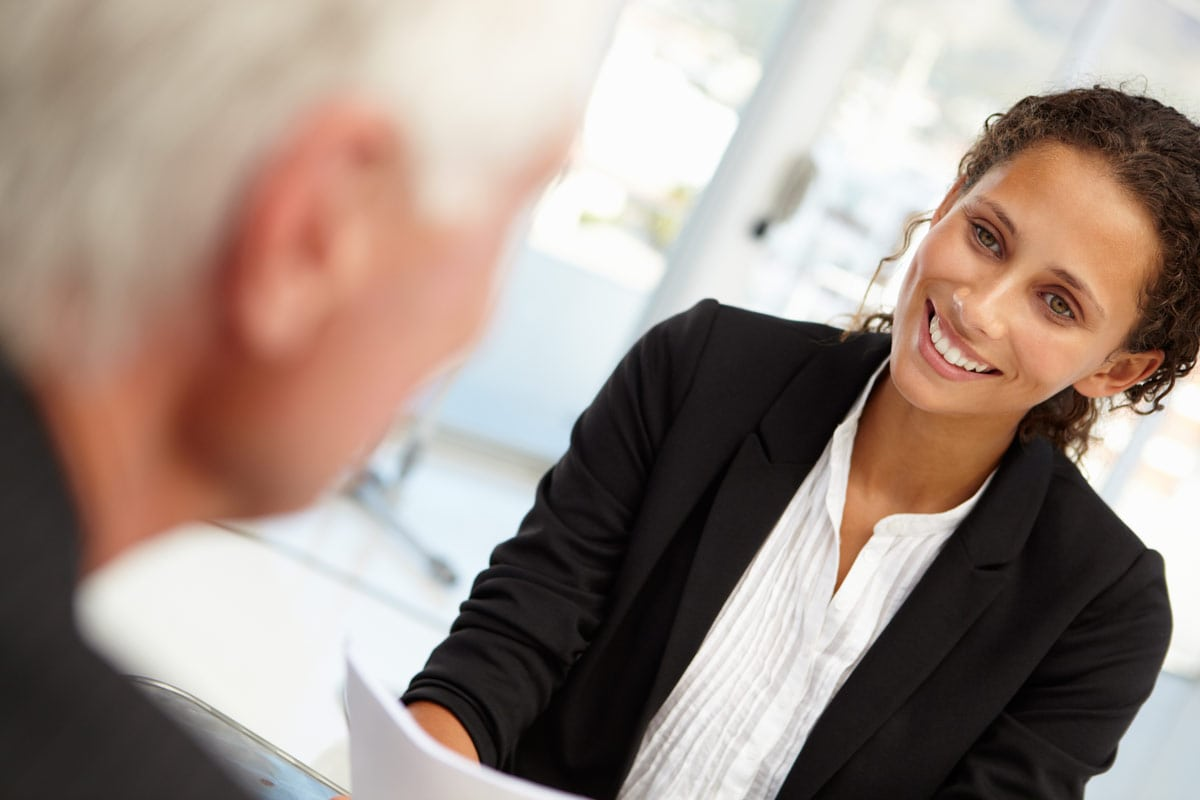 Woman interviewing older man for a sales position