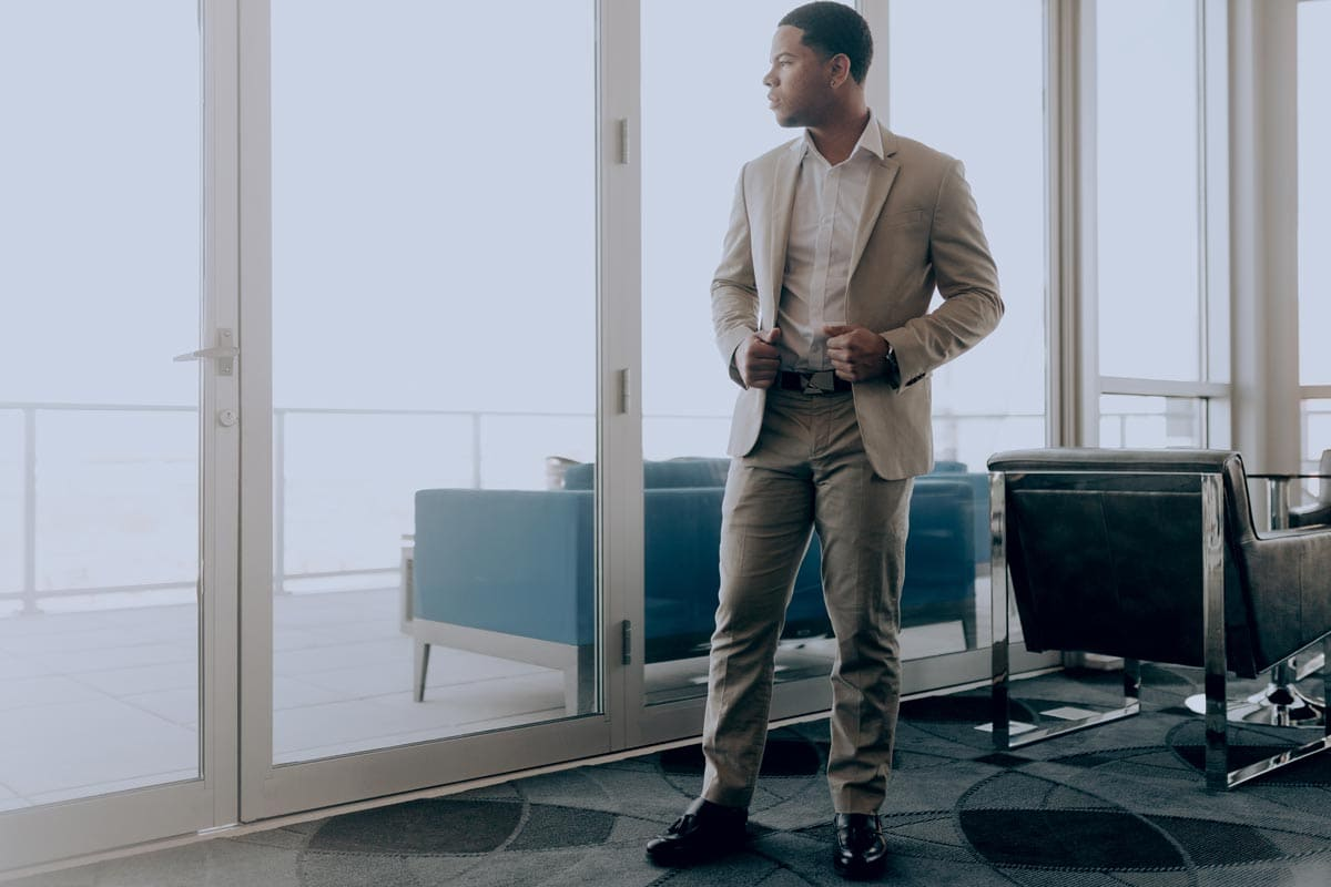 Image of man in a tan suit at a fancy office waiting for an interview